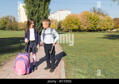 Two primary school students boy and girl with backpacks going to school, back to school, autumn outdoor. Education, friendship, and people concept - Stock Photo