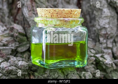 Glass bottle with cork cap with green-yellow nectar oil. Located on the bark of coniferous wood. The concept of the use of natural ingredients in cosm - Stock Photo