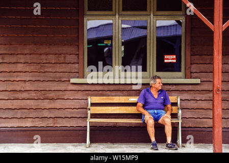 New Zealand, South Island, Arrowtown. A tourist takes a rest sitting on a bench. A historic gold mining town in the Otago region. Photo taken November - Stock Photo