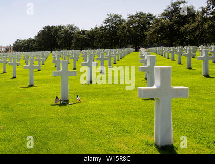 American and French flags in the middle of the graves of American soldiers who fell during the Battle of France in Normandy - Stock Photo