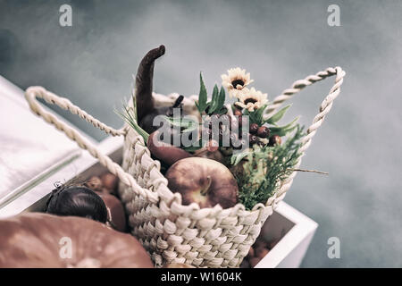 Home festive flower arrangement from leaves, flowers, vegetables, fruits, berries in the rustic wicker basket. Autumn holidays - Stock Photo