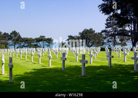 Alignment of graves of American soldiers who died during the Battle of France in Normandy, the sea of Omaha Beach in the background - Stock Photo