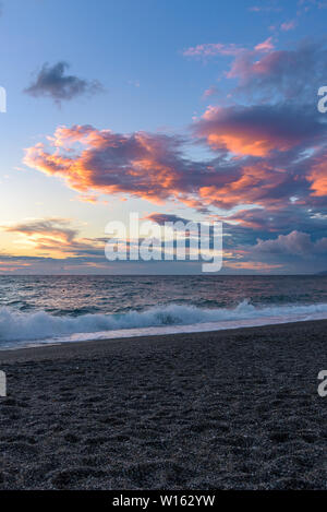Picturesque sunset on the Calabrian beach in Italy - Stock Photo