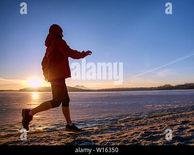Young woman running along the shore of a frozen lake in winter spring. Regular training run, keep high level of condition. - Stock Photo