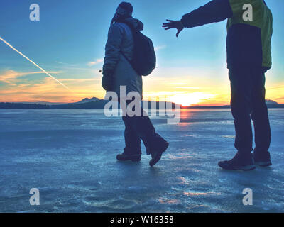 Couple holding by hands. Beautiful young couple in puffy jackets holding hands and enjoying winter daybreak, hiking at frozen pond or lake