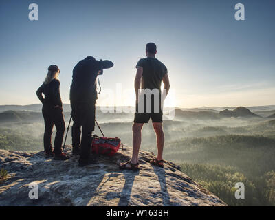 Three friends photographers discuss and taking photo against sunset sky from sticking out rock above misty pandscape. Photographers backpacker and hik - Stock Photo