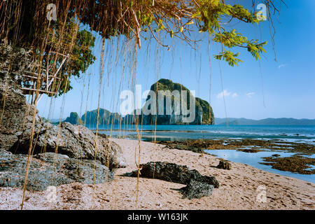 Philippines natural scenery beach at low tide, wooden bower at the tree, amazing Pinagbuyutan island in background. Exotic nature sea shore in El Nido - Stock Photo