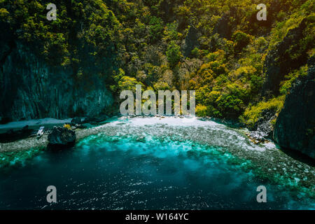 El Nido, Palawan, Philippines, aerial view of banca boat, karst mountain wall pristine sand beach and coral reef, great secret island hopping location - Stock Photo