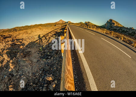 Fish eye lens shot of Sunset time above the clouds in the mountains. Fresh lava fields. Park road the road is far away. View of Dog Head mountain on h - Stock Photo