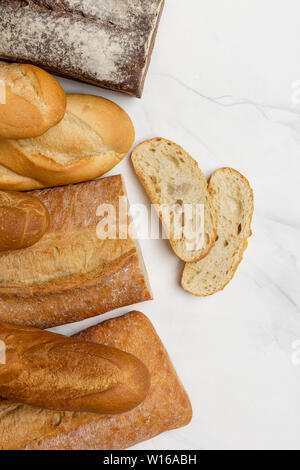 Wholegrain, white and brown bread with slices on white background, vertical top view, free space for text - Stock Photo