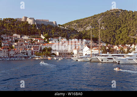 Hvar Town and its harbor as seen from a sea approach.  This Adriatic playground attracts celebrities and mega-yachts. - Stock Photo