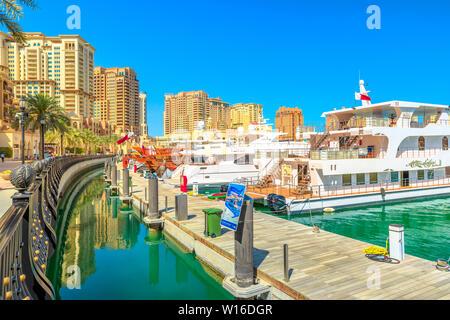 Doha, Qatar - February 18, 2019:Marina corniche promenade in Porto Arabia at the Pearl-Qatar, Doha, with residential towers and luxury boats and - Stock Photo