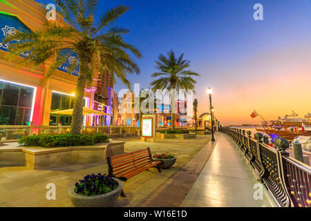 Doha, Qatar - February 18, 2019:Palm trees in walkway of Porto Arabia at the Pearl-Qatar, Doha, with skyscrapers of West Bay skyline at sunset sky - Stock Photo
