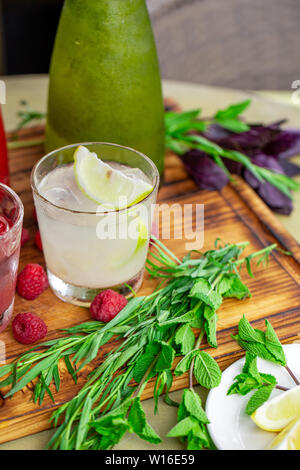 Summer soft drinks, a set of lemonades. Lemonades in jugs on the table, the ingredients of which they are made are arranged around. - Stock Photo