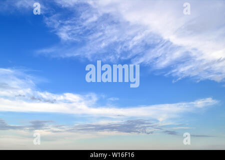 White cirrus and stratus clouds high in the blue summer sky. Different cloud types and atmospheric phenomena. Skyscape on a sunny day. - Stock Photo