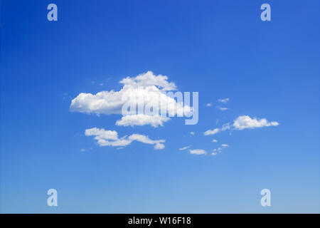 Scenic group of white fluffy cumulus clouds high in the blue summer sky. Different cloud types and atmospheric phenomena. Skyscape on a sunny day. - Stock Photo