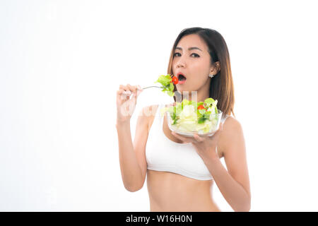 Beautiful asian young woman healthy food in white sport bra eating salads with healthy food on a white background. - Stock Photo