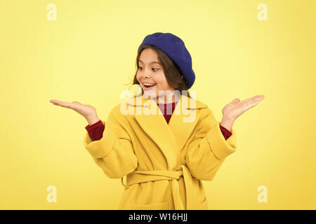 Child promoting something yellow background copy space. Place for ad advertisement. Girl show open palm. Advertising product. Look at this. Advertisement launching product. Advertisement concept. - Stock Photo