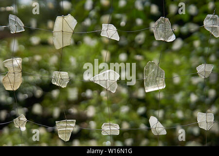 background pattern of glass shards tied in a grid with thin wire and green bokeh behind - Stock Photo