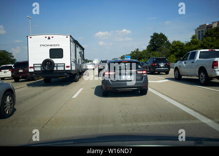 traffic tailbacks at peak rush hour driving around indianapolis as joining cars leave sliproad onto interstate USA - Stock Photo