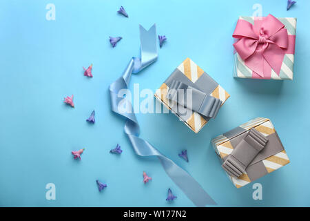 Beautiful gift boxes and flowers on color background - Stock Photo