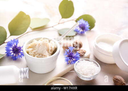 Shea butter with cosmetic products on table - Stock Photo