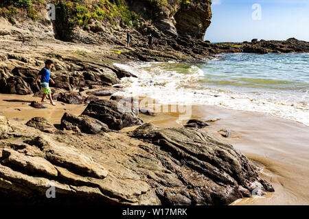 Laguna Beach, CA / USA - May 4, 2019: Little boy walking on the rocky shore during low tide at Crescent Bay Beach. - Stock Photo