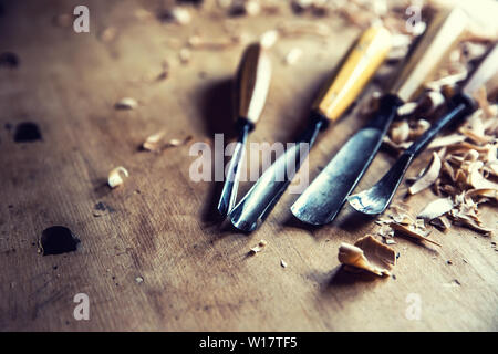 Woodworking vintage tools chisels with wood shawings on retro workbench - Stock Photo