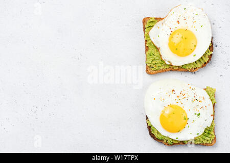 Toast with mashed avocado and sunny side up egg on grey concrete background. Table top view, healthy food, clean eating concept - Stock Photo