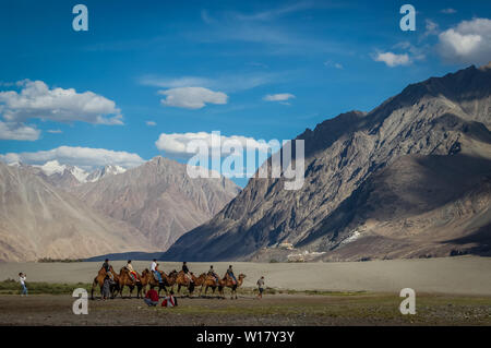 Ladakh, India; Dated- May 14, 2019: Tourists enjoying camel ride in the cold desert of Ladakh. Ladakh landscape with desert mountains and blue sky - Stock Photo
