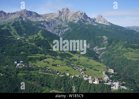 SKI RESORT OF LE SAUZE IN SUMMER DOMINATED BY THE 'CHAPEAU DU GENDARME' PEAK (elevation: 2682m) (aerial view). Enchastrayes, Ubaye Valley, France. - Stock Photo