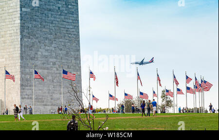 Washington D.C., USA, October 2016; people visiting the Washington Monument with a commercial airplane landing in the background - Stock Photo