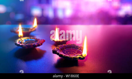 Happy Diwali - Colorful clay diya lamps lit during diwali celebration - Stock Photo