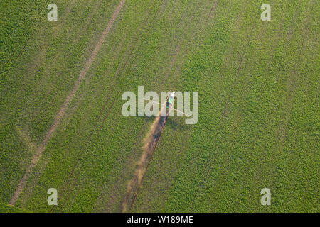 Aerial view of a farm tractor in a green field during spraying and irrigation with pesticides and toxins for growing food, vegetables and fruits. Agri - Stock Photo