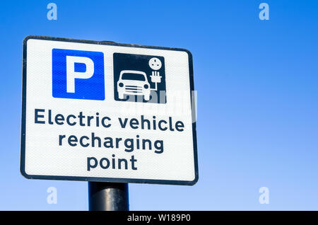 Recharging point for electric car sign against clear sky - Stock Photo