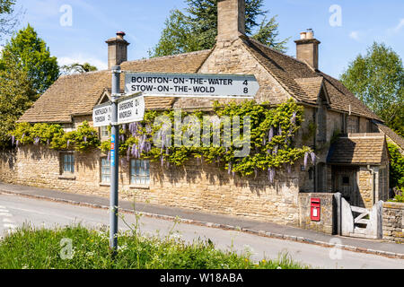 Maytime in the Cotswolds - A road sign on the village green in the Cotswold village of Farmington, Gloucestershire UK - Stock Photo