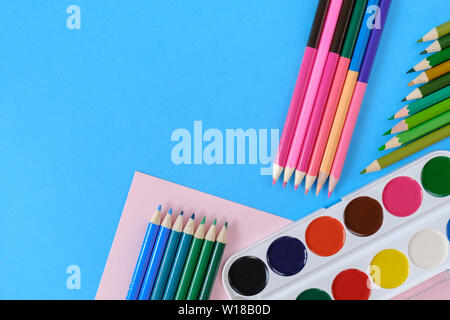 Back to school concept. School equipment with colored pencils and watercolor on blue background. Flat lay, top view, copy space. - Stock Photo