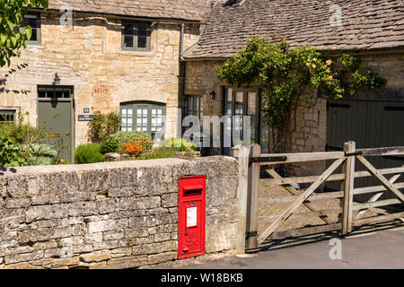 A bright red post box let into the wall outside The Old Forge in the Cotswold village of Windrush, Gloucestershire UK - Stock Photo