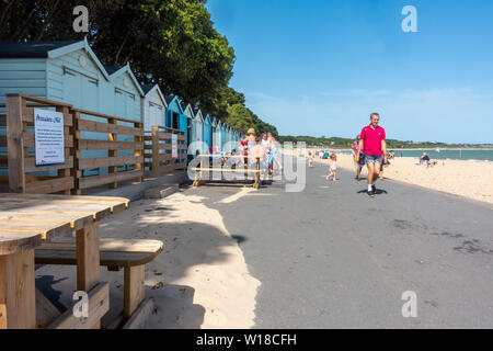 Row of beach huts in different pastel blue shades run along the top of Avon Beach at Mudeford, Christchurch in Dorset, UK. A sandy beach with pebbles.