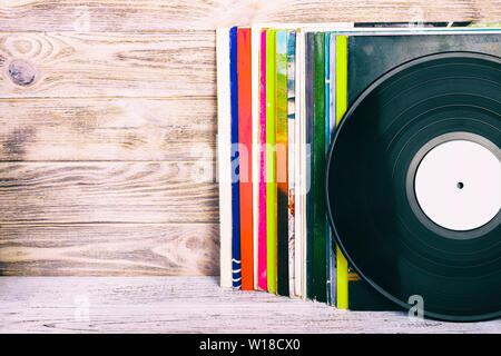 Retro styled image of a collection of old vinyl record lp's with sleeves on a wooden background with Copy space toned. - Stock Photo