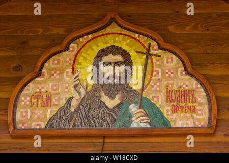 Mosaic orthodox icon of John the Baptist on the wooden wall of the temple - Stock Photo