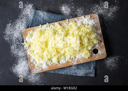 Grated boiled potatoes with flour for the preparation of an Italian dish - potato gnocchi. Black background. - Stock Photo
