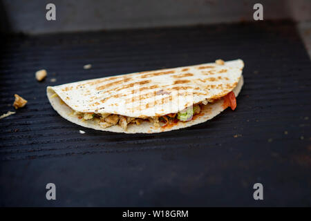 Healthy and hearty food, fajita with grilled chicken fillet, avocado, fresh salsa, served very hot, from grill. Concept of healthy fast food - Stock Photo