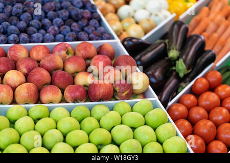 Assorted fruits and vegetables in a tray on the market - Stock Photo
