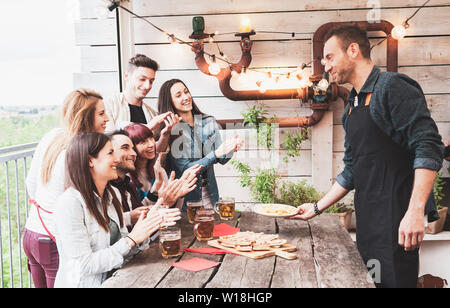 Happy group of friends drinking beer and eating pizza at brewery bar restaurant. concept with young people having genuine fun - Stock Photo