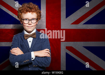 Smart child in suit and glasses on the UK flag background. English language school concept - Stock Photo