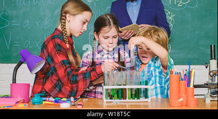 back to school. kids in lab coat learning chemistry in school laboratory. chemistry lab. making experiment in lab or chemical cabinet. happy children teacher. Hard to diagnose. - Stock Photo