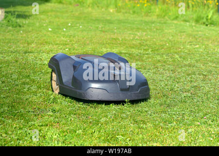 robotic lawnmower on the grass in garden - Stock Photo
