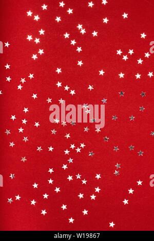 Silver stars glitter on red background. Festive holiday pastel backdrop. - Stock Photo