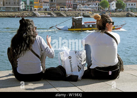 Two women rear view back behind sitting on the quayside with lululemon bag on the River Douro in Ribeira Porto Oporto Portugal Europe EU KATHY DEWITT - Stock Photo